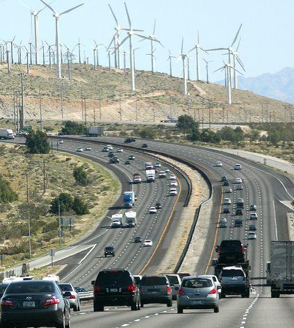 a wind turbine farm above a freeway